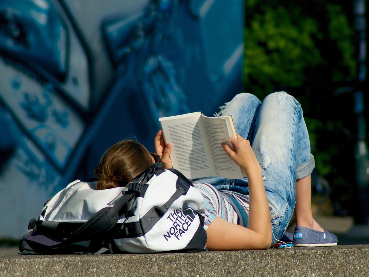 woman reading, rucksack, lying on ground